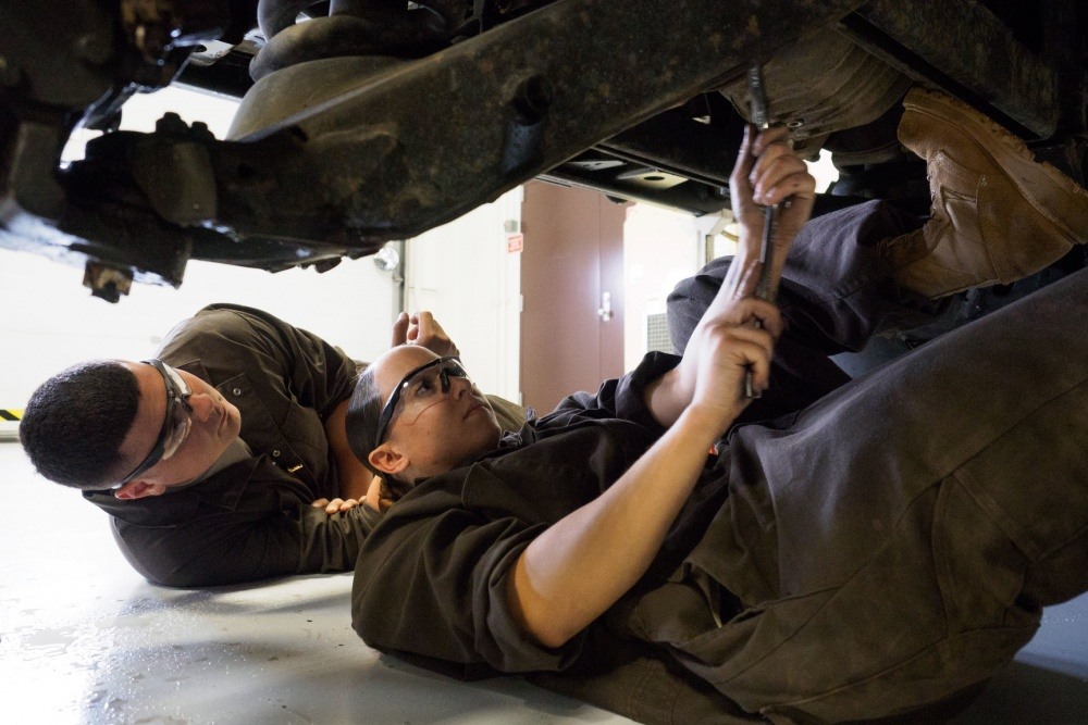 Arizona Army National Guard Spc. Eriberto Paredes, a utility equipment repairer works under a with Spc. Sabrina Carrico, a wheeled-vehicle mechanic, as Carrico