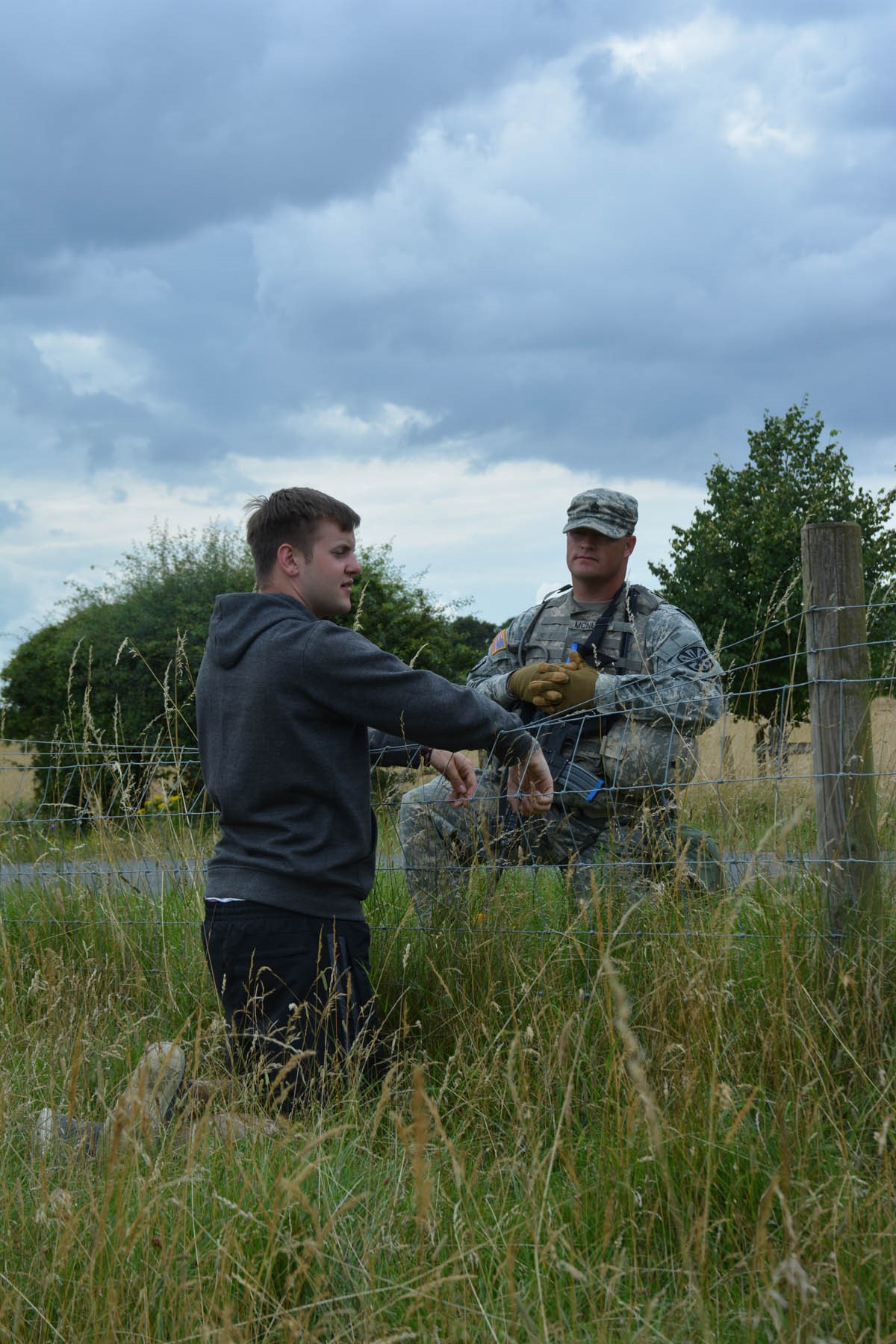 "Army Staff Sgt. Casey McNutt, squad leader 856th MP Co., Arizona Army National Guard, speaks with a ""villager"" during a patrol on Stanford Training Area, United Kingdom, during Steppe Eagle 16"