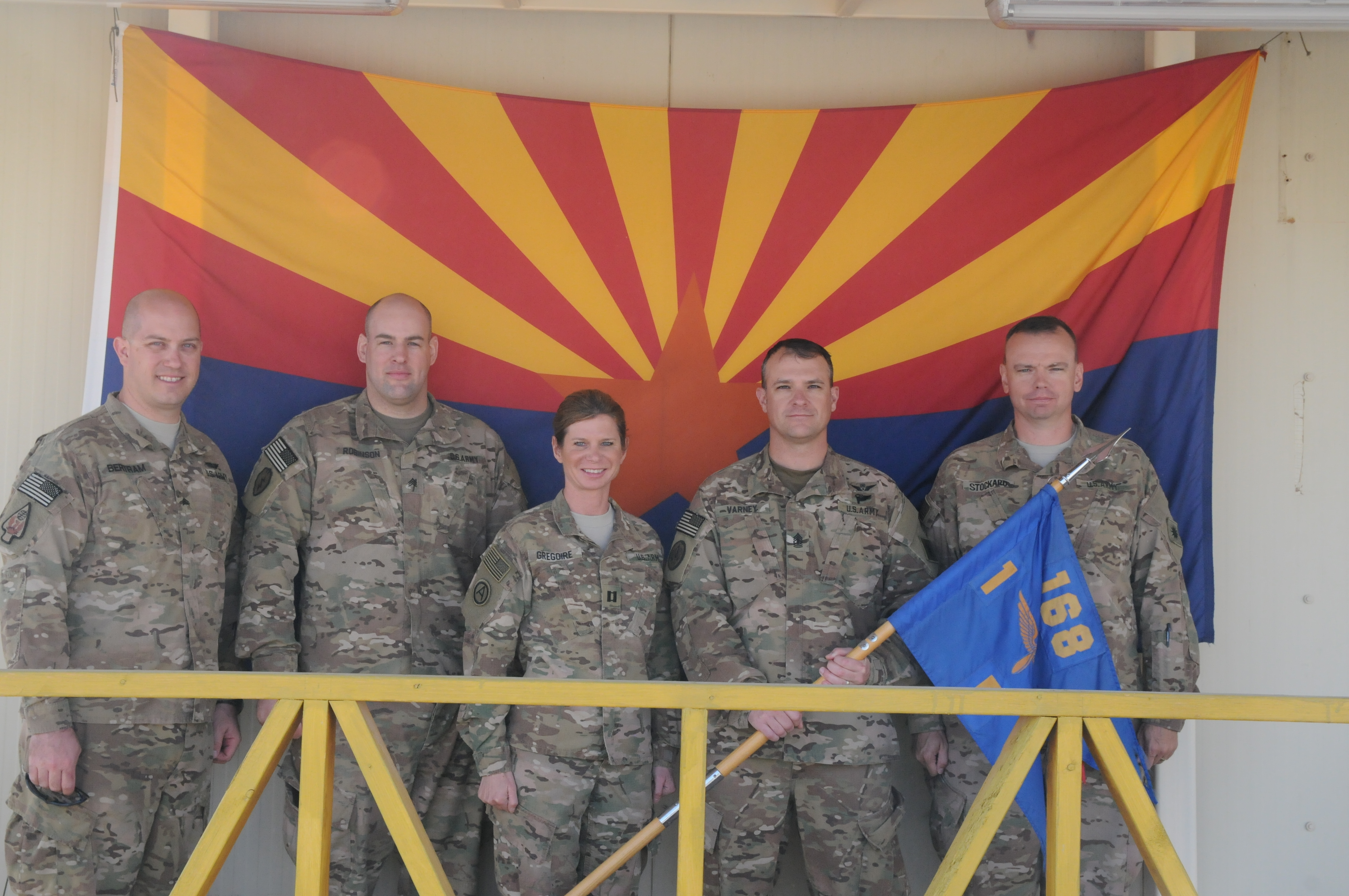 arizona guardsmen stand in front of the arizona flag while deployed to Kuwait