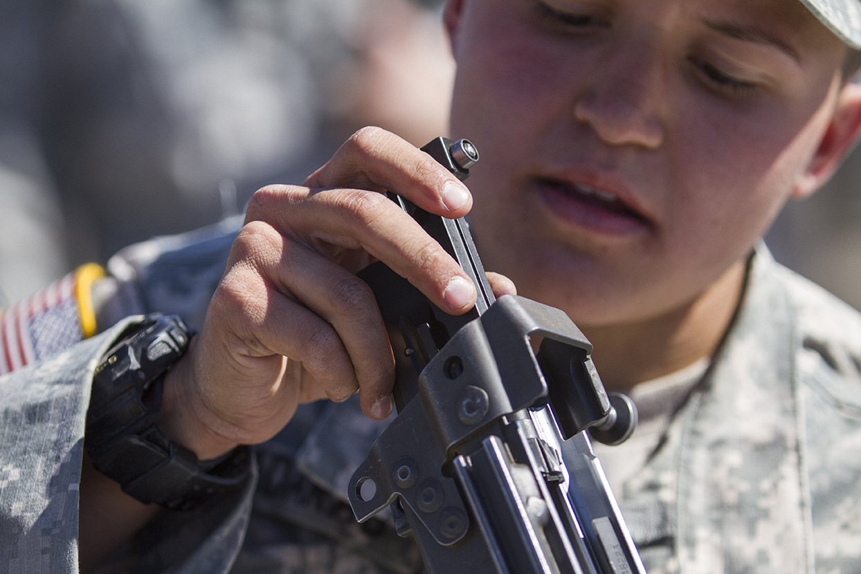 a female soldier attempts to reassemble a machine gun