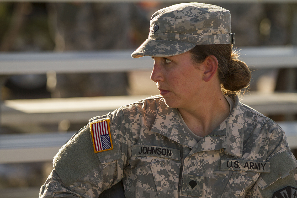 A female soldier speaks with other soldiers as she prepares for a land navigation event