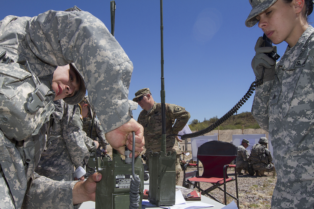 a male soldier attempts to assemble a radio while a female judge looks on