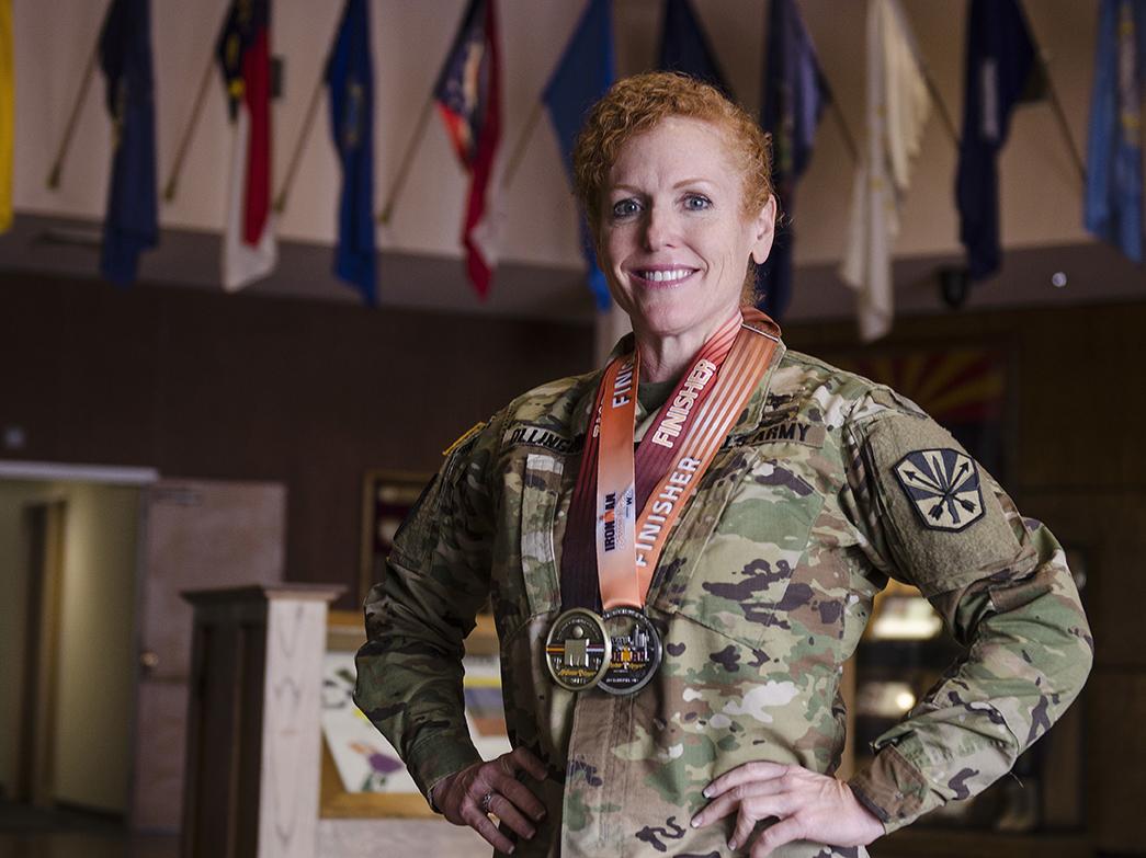 Lt. Col. Zoe Ollinger stands with her medals from past triathlons