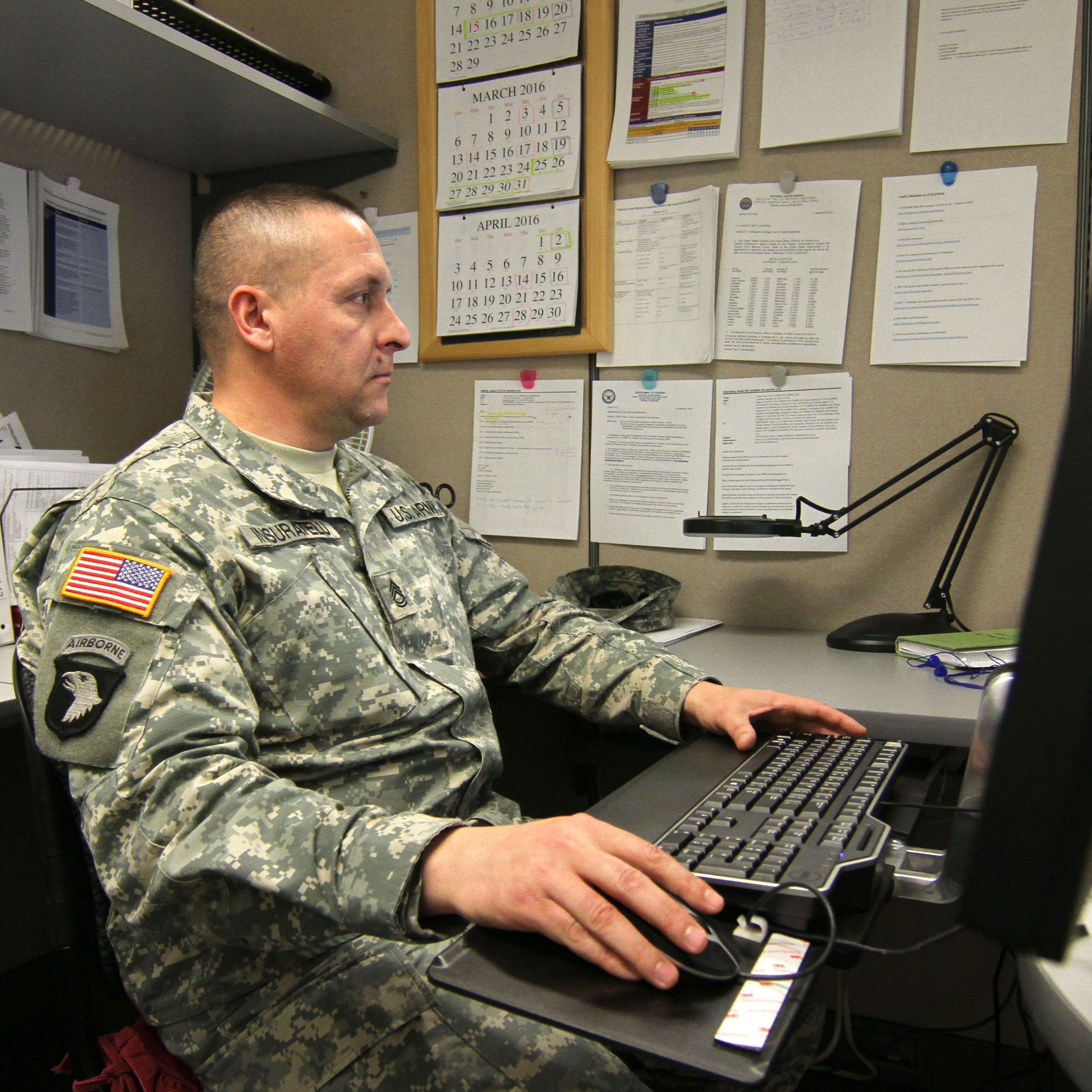 A USPFO Employee sits at a computer doing work