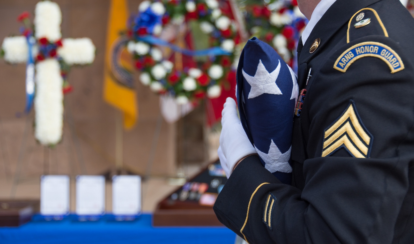 A soldier hands a family member of a fallen soldier a folded American flag