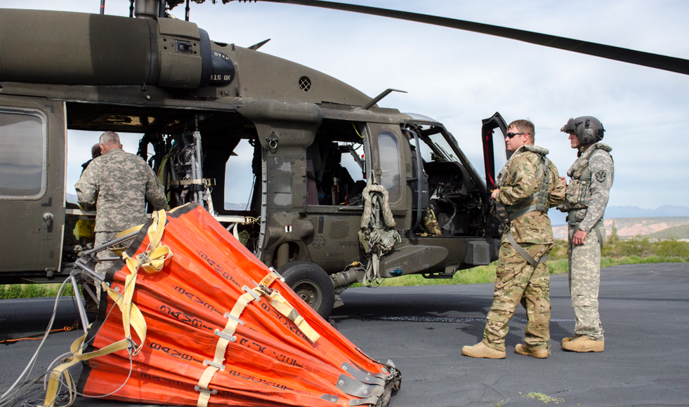 Arizona National Guard members prepare helicopter water drop bucket for wildfire exercise.