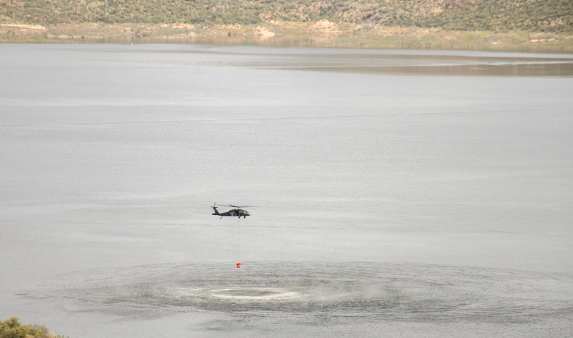 Black Hawk helicopter lowers water bucket into Roosevelt Lake for wildfire exercise.