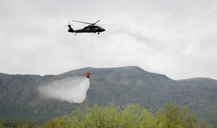 Black Hawk helicopter releases water onto practice targets during wildfire exercise.