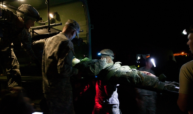 A team of Medics offload a notional patient out of a military ambulance.