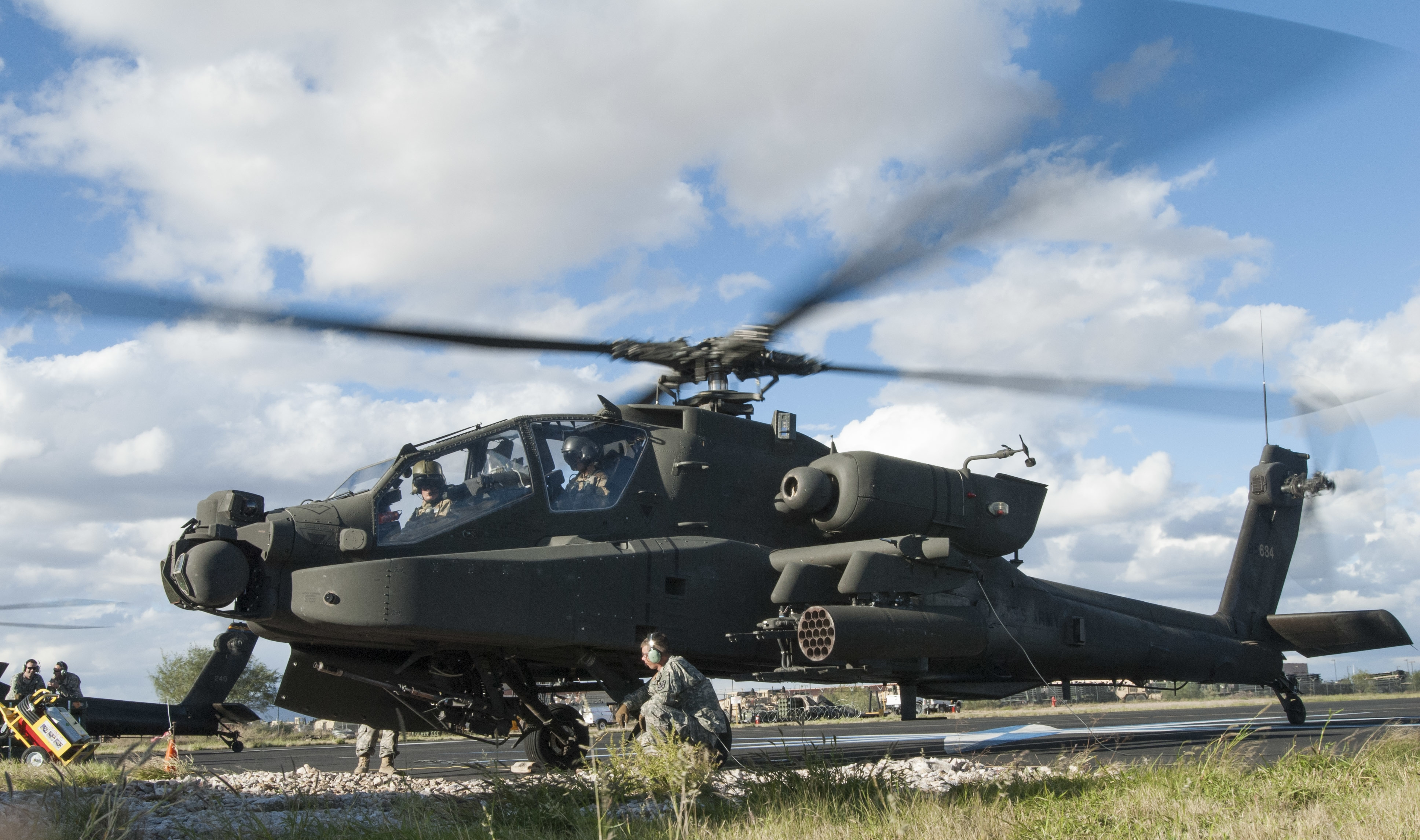 An AH-64D Apache Attack Helicopter prepares to be loaded with ammunition
