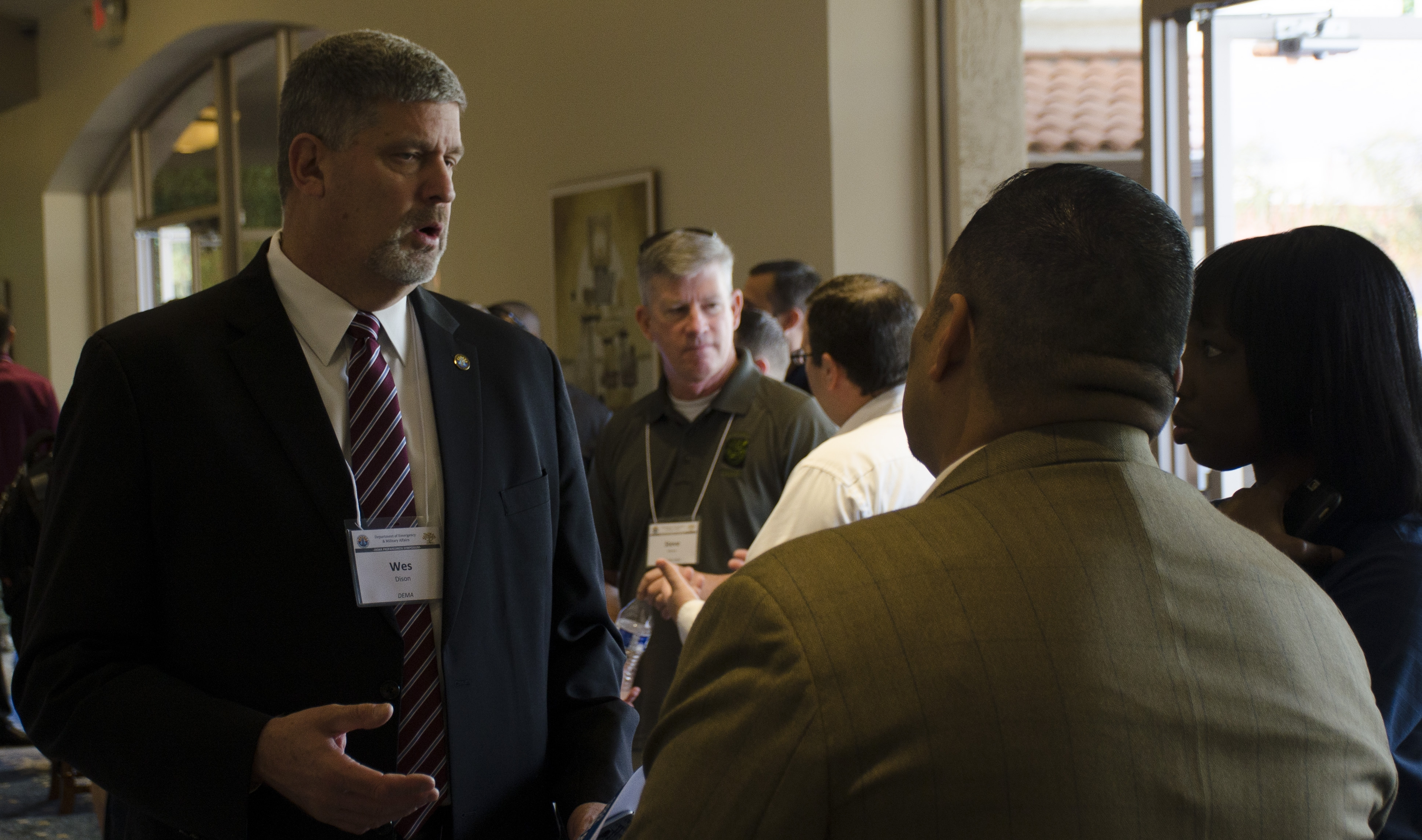 Emergency Management professionals stading and talking in a group during a conference.