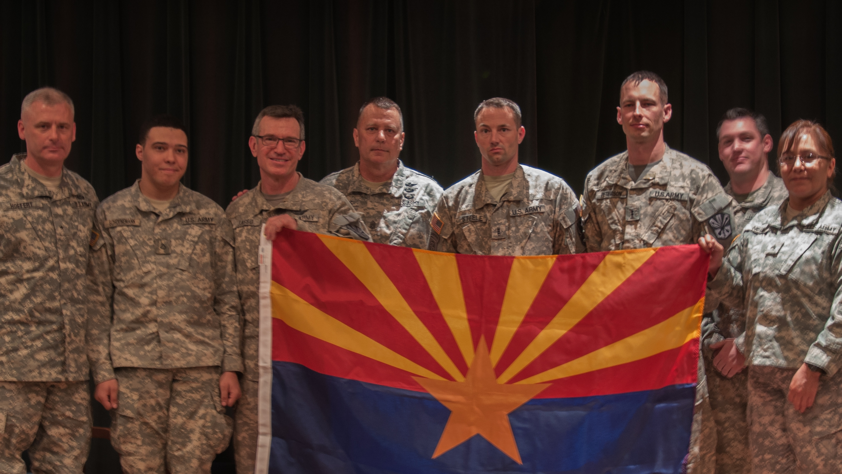 Soldiers from the Arizona Army National Guard's Det. 31 Operational Support Airlift Agency holding an Arizona state flag.