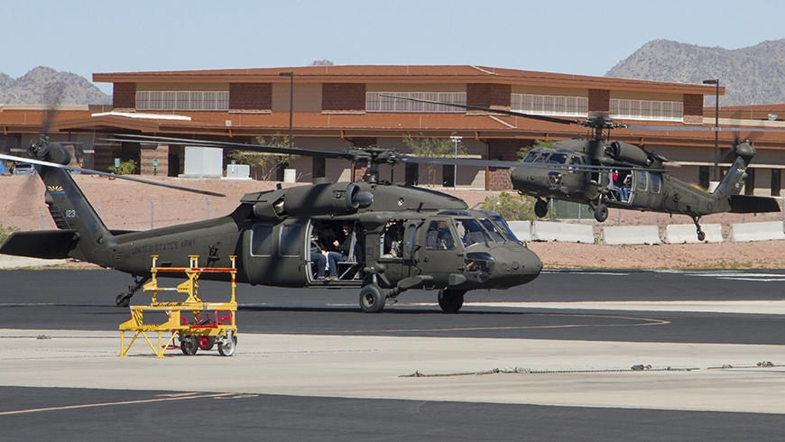 Two UH-60 Black Hawks land at Papago park Military reservation with a building in the background