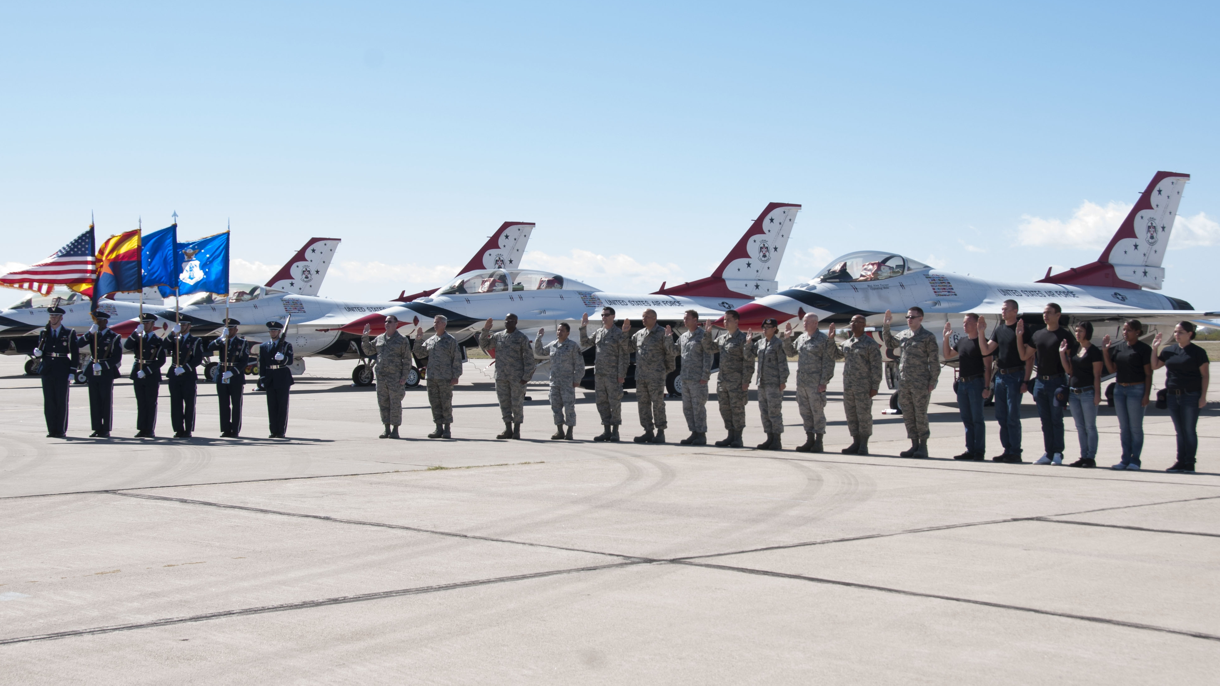 Airmen stand in front of Air Force plnes as they swear the oath of enlistment