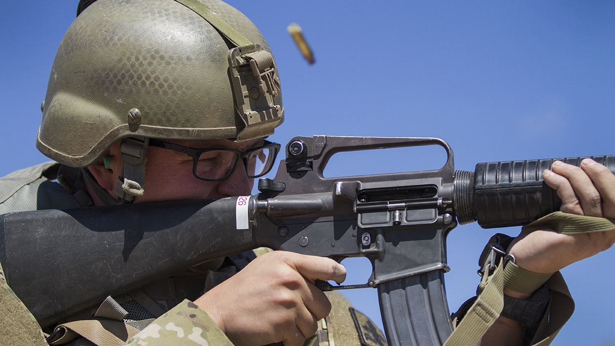 a brass bullet casing is ejected from a soldiers rifle as he fires at pop up targets