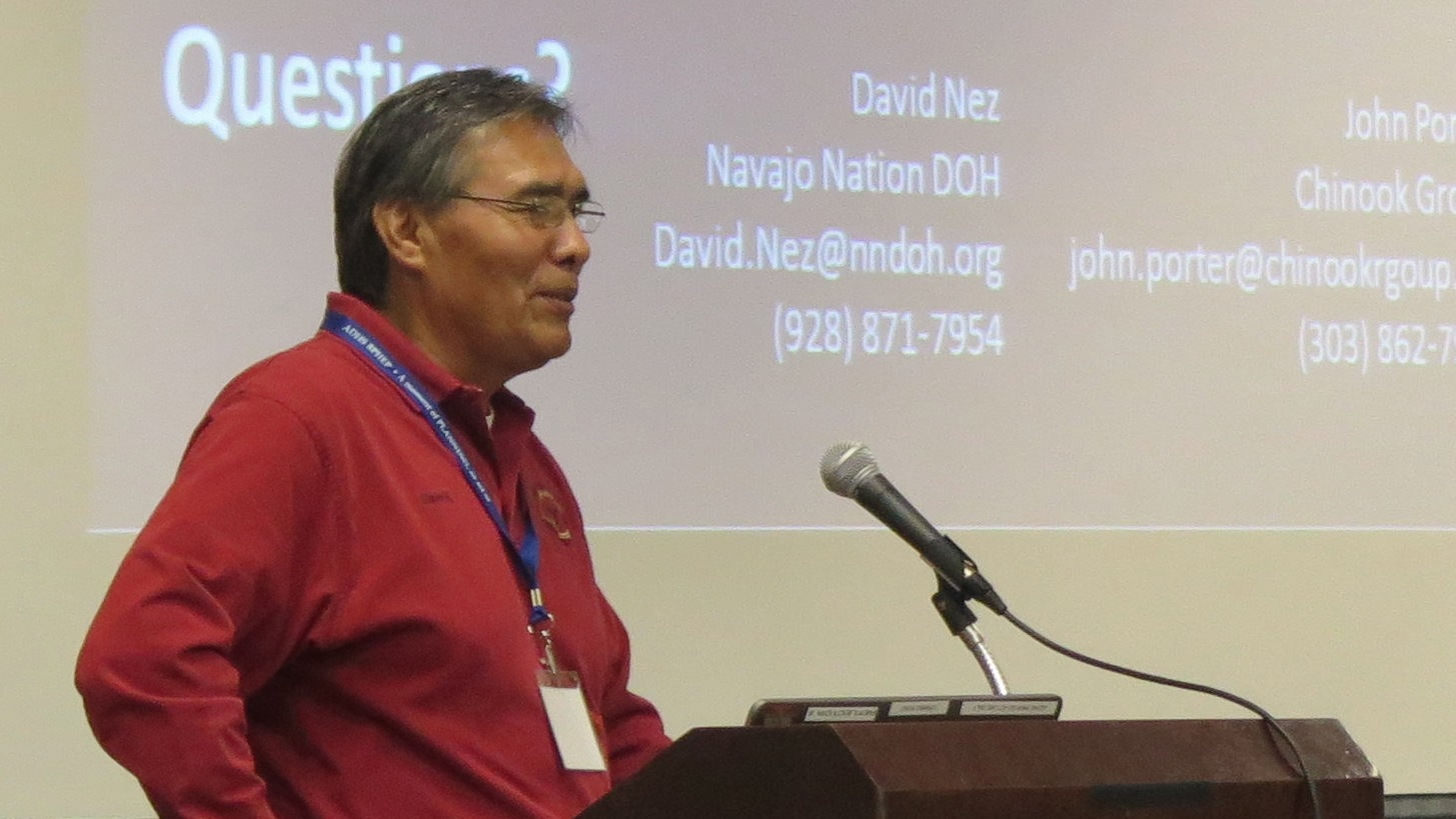 A Navajo Nation Department of Health representative stands behind a podium in a red long sleeve shirt and glasses, as he addresses a group of emergency managers during the 2017 Tribal Emergency Preparedness Summit.