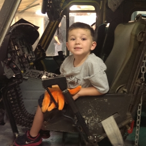Young boy sits in a Huey cockpit