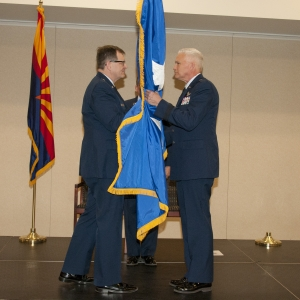 Major General Michael T. McGuire, the Adjutant General of Arizona, hands a two-star guide-on to newly promoted Maj. Gen. Edward Maxwell, the Air Component Commander, at his promotion ceremony at Papago Park Military Reservation Jan. 10.