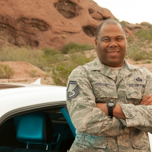 Senior Master Sgt. Hudgins poses with arms crossed standing next to a white car.