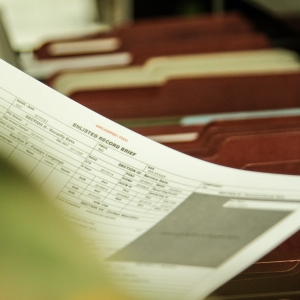 Soldier hold Enlisted Records Brief by open file cabnet