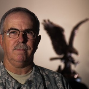 Portrait of CW5 John Vitt with Eagle in background over his left shoulder