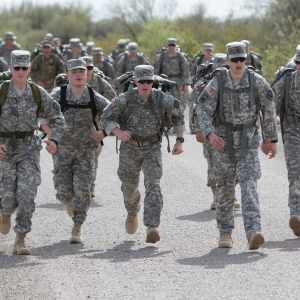 Soldiers and cadets marching on gravel during a ruck march