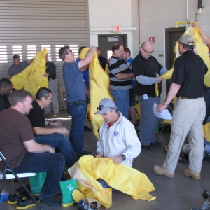 Students in the Operations Level Response to HazMat/WMD Incident course practice putting on protective suits.