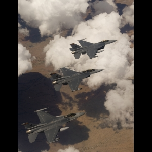 F-16 fighter planes fly over clouds