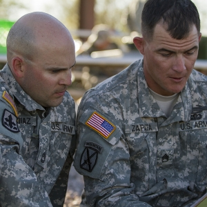 two soldiers study a map prior to a land navigation event