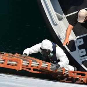 An Arizona Guardsman in a HAZMAT suit climbs up a ladder from one boat to another