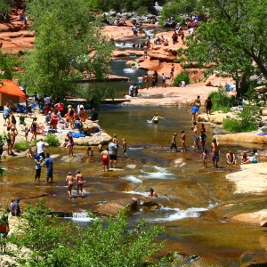 Families enjoying Slide Rock State Park in summer.